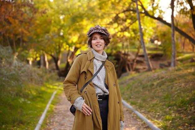 Modna młoda piękna brązowowłosa kobieta z fryzurą bob, ubrana w modny płaszcz wielbłąda, dzianinowy poloneck i czapkę lamparta, stojąc nad miejskim ogrodem