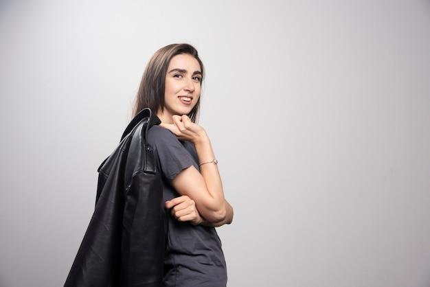 Modna młoda piękna kobieta pozuje w czarnej skórzanej kurtce.