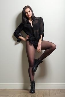 Modna młoda piękna kobieta pozuje w czarnych nylonowych rajstopach, stylowych skórzanych butach i czarnej bluzce