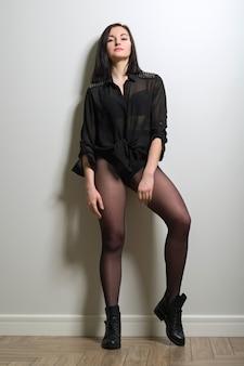 Modna młoda piękna kobieta w czarnych nylonowych rajstopach, stylowych skórzanych butach i czarnej bluzce