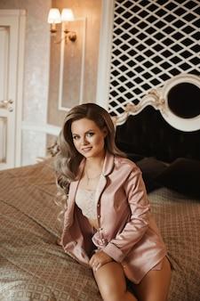 Modna młoda piękność w modnej bieliźnie nocnej siedzi na łóżku.
