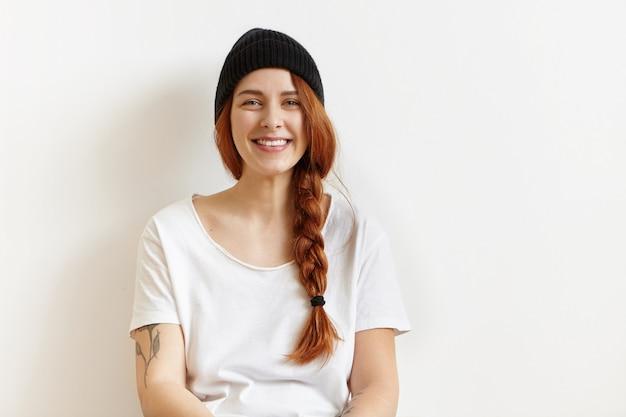 Modna młoda ruda kobieta z warkoczem i tatuażem na ramieniu po odpoczynku w pomieszczeniu