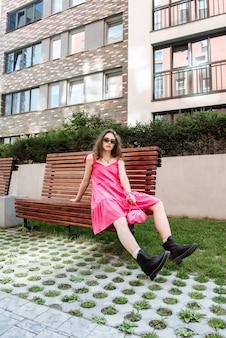 Modna modelka pozuje na ławce w nowej kolekcji ubrań