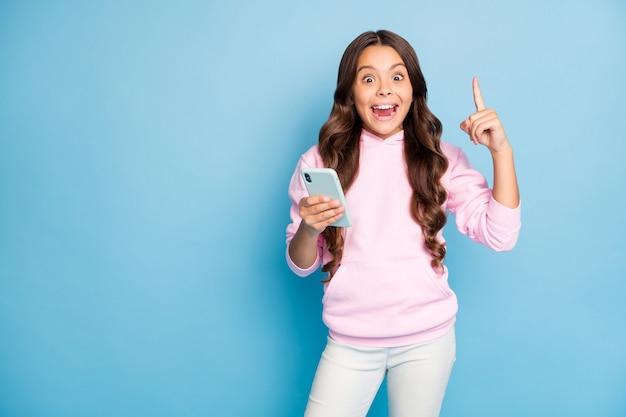 Modna nastolatka pozuje przed niebieską ścianą