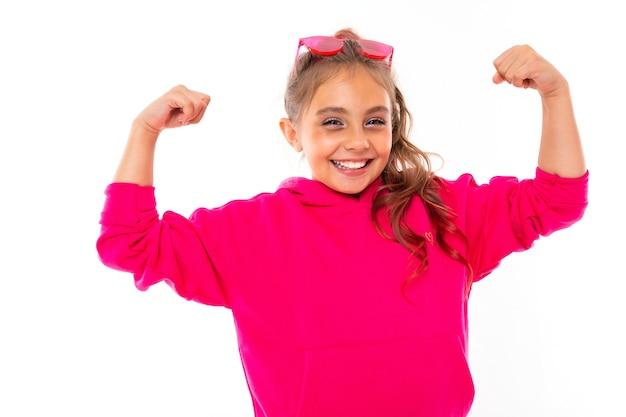 Modna nastolatka w różowej bluzie z kapturem iz różowymi okularami przeciwsłonecznymi gestykuluje, portret na białym tle