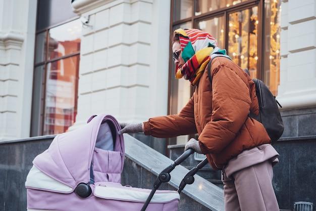 Modna nowoczesna mama z wózkiem na spacerze po mieście, jesień