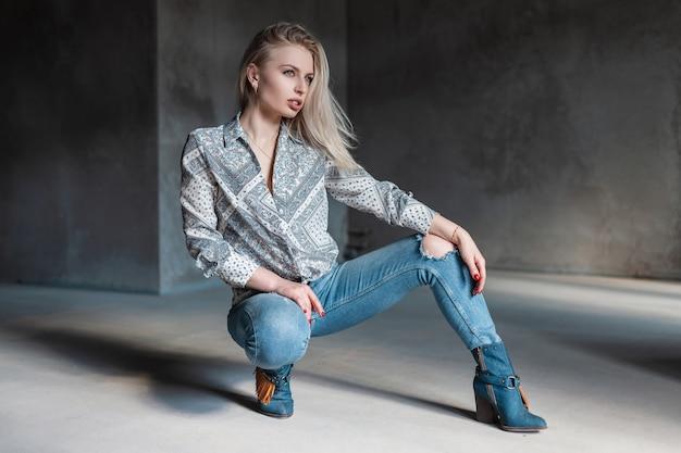 Modna, nowoczesna młoda kobieta blondynka w stylowej koszuli w modnych podartych dżinsach w kowbojskich butach vintage pozowanie, siedząc w pokoju z promieniami słonecznymi