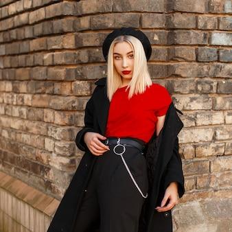 Modna, nowoczesna młoda kobieta blondynka z czerwonymi ustami w stylowe ubrania w stylu retro pozuje w pobliżu zabytkowego budynku z cegły