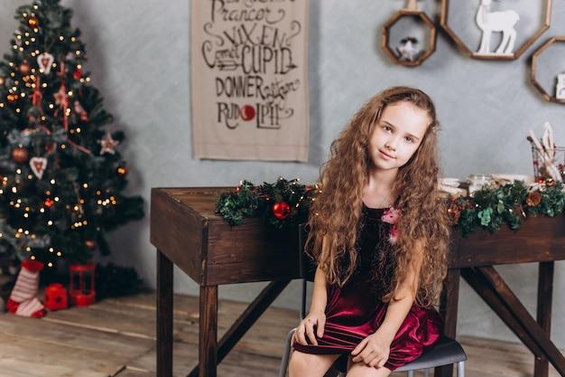 Modna piękna dziewczyna w sukni w domu w pobliżu sylwestra i ozdób choinkowych i kolorowych świateł
