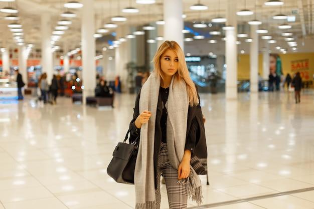 Modna piękna kobieta w modnym szarym płaszczu z szalikiem i czarną torbą w centrum handlowym
