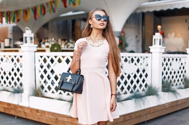 Modna piękna kobieta w okularach przeciwsłonecznych, różowa sukienka z torbą w pobliżu białego ogrodzenia
