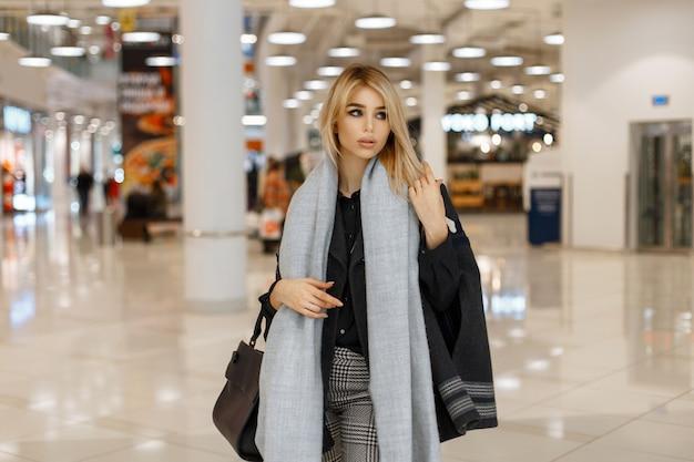 Modna piękna kobieta w stylowym jesiennym płaszczu z szalikiem robi zakupy w centrum handlowym