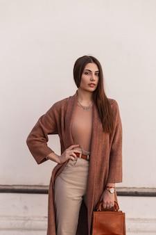 Modna piękna młoda dziewczyna w stylowej odzieży wierzchniej z płaszczem i skórzaną torebką