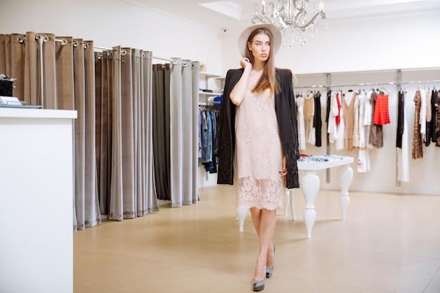 Modna piękna młoda kobieta stojąca w sklepie odzieżowym