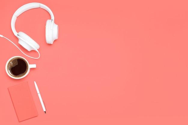 Modna, płaska kompozycja z koralowym pamiętnikiem, białym długopisem, białą filiżanką kawy i białymi słuchawkami