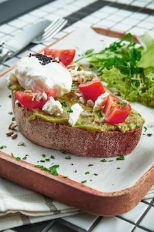 Modna przekąska uliczna. smaczne tosty z awokado na papierze rzemiosła na białym stole. odżywianie wegetariańskie. zamknąć widok