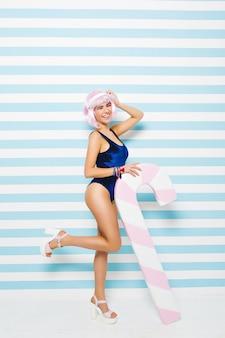 Modna radosna młoda kobieta z ciętą różową fryzurą, bawiąca się dużym lizakiem na pasiastej ścianie. lato, szpilki, seksowny wygląd, stylowy niebieski kostium kąpielowy, wyrażający pozytywność.