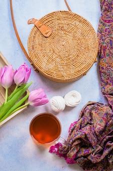 Modna rattanowa torba, filiżanka herbaty, tulipany i szalik na jasnym tle.