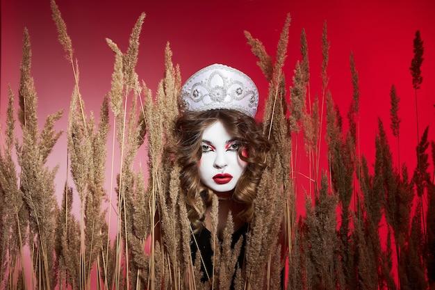 Modna rosjanka w kokoszniku z samowarem na czerwonym tle, jasny makijaż