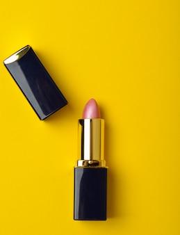 Modna różowa szminka i kopiejka na żółtym pastelowym tle. minimalistyczna moda. spraw, by twoje usta były kuszące.