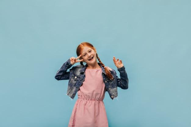 Modna ruda dziewczyna z piegami w kurtce i różowej nowoczesnej sukience pokazująca znak pokoju i uśmiechająca się na izolowanej ścianie