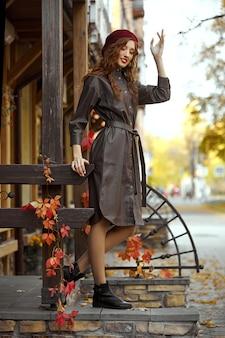 Modna ruda kobieta w bordowym berecie i skórzanym płaszczu przeciwdeszczowym stoi jesienią na ganku.