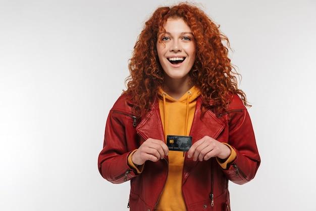 Modna ruda kobieta w wieku 20 lat w skórzanej kurtce uśmiechnięta i trzymająca plastikową kartę kredytową na białym tle nad białą ścianą