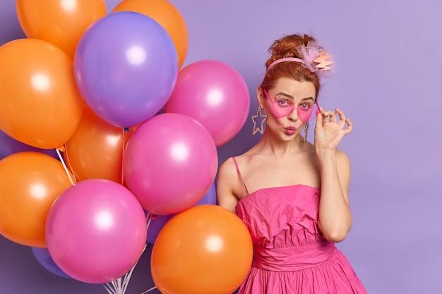 Modna rudowłosa młoda kobieta wygląda z romantycznym wyrazem twarzy w cmaera, dzięki czemu usta są zaokrąglone