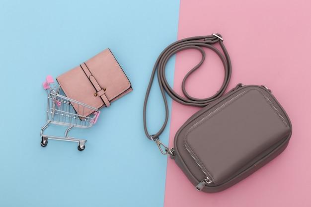 Modna skórzana torba i portfel z wózkiem na zakupy na różowym niebieskim pastelowym tle. koncepcja zakupów. widok z góry.