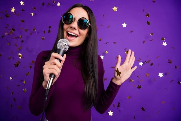 Modna śliczna atrakcyjna gwiazda rocka śpiewa do mikrofonu, reprezentując jej nową piosenkę na białym tle żywej ściany koloru