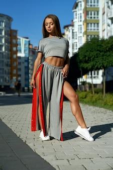 Modna sportowa kobieta pozuje w pobliżu budynków wielokondygnacyjnych