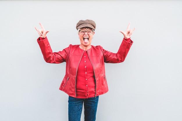 Modna starsza kobieta tanczy muzykę rockową jest ubranym modne ubrania
