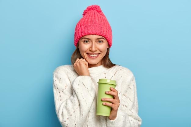 Modna studentka pije kawę na wynos, nosi ciepłe stylowe ubrania, ma przerwę po wykładach, pozuje na niebieskiej ścianie