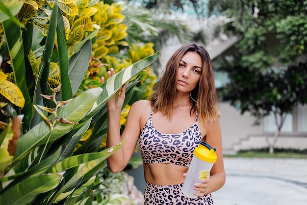Modna, stylowa młoda kaukaska sportowa kobieta w bluzce w panterkę i spodenkach motocyklowych na zewnątrz trzyma shaker proteinowy