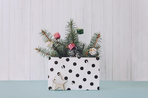 Modna stylowa świąteczna kompozycja z torbą na prezenty, gałązkami jodły