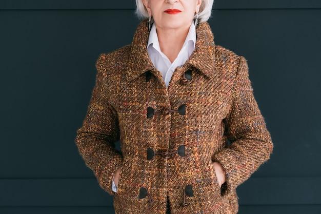 Modna szafa seniora. kobiecy styl i elegancja. wieku pani pozowanie w stroju jesień moda tweed z rękami w kieszeniach.