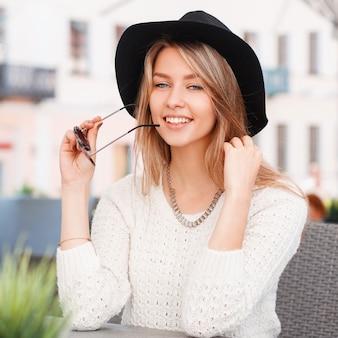 Modna szczęśliwa młoda hipster kobieta w stylowy sweter z dzianiny w modnych okularach przeciwsłonecznych w eleganckim czarnym kapeluszu siedzi w kawiarni w słoneczny letni dzień. bardzo wesoła dziewczyna blondynka.