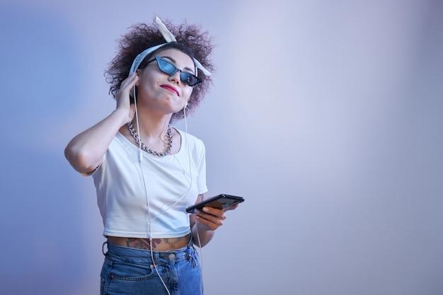 Modna, szczęśliwa uśmiechnięta dziewczyna z lokami w stylu afro słucha i lubi muzykę w słuchawkach