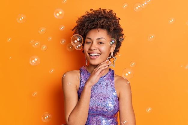 Modna, wesoła afroamerykańska dama delikatnie dotyka linii szczęki, ma modną fryzurę, uśmiecha się szeroko, nosi stylową błyszczącą fioletową koszulę kolczyki w kształcie gwiazdy pozuje na pomarańczowej ścianie z bańkami mydlanymi