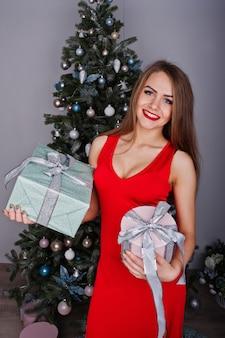 Modna wspaniała kobieta w czerwonej długiej wieczorowej sukni pozuje przeciw drzewu noworocznemu z prezentami. motyw świąt bożego narodzenia.