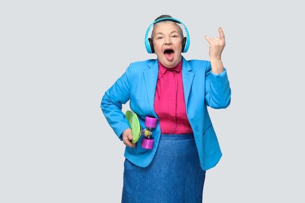 Modna zabawna babcia w stylu casual z niebieskimi słuchawkami trzymająca zieloną deskorolkę słuchać muzyki pokazującej znak rocka tougue się, patrząc na kamery. wewnątrz, studio strzał, na białym tle na szarym tle