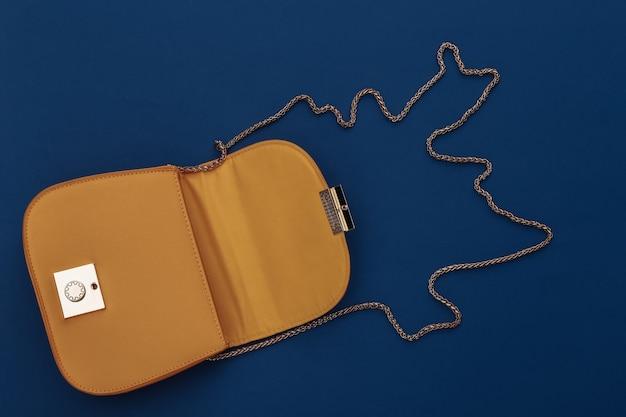 Modna żółta skórzana torebka na klasycznym niebieskim tle. kolor 2020. widok z góry.