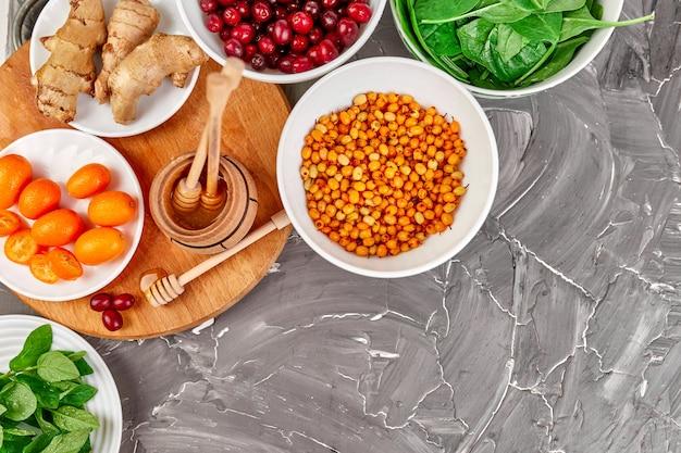 Modna żywność chroniąca przed wirusami, koronawirus, koncepcja odporności. asortyment bogaty w przeciwutleniacze i źródła witamin na szarej ścianie, koncepcja diety zdrowej żywności.