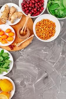 Modna żywność chroniąca przed wirusami, koronawirus, koncepcja odporności. asortyment produktów bogatych w przeciwutleniacze i źródła witamin na szarym tle, koncepcja diety zdrowej żywności.