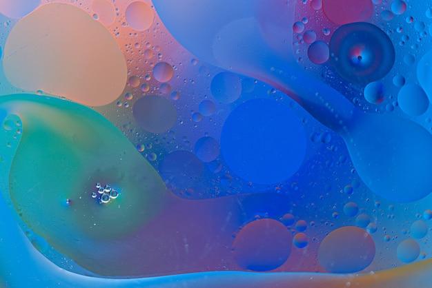 Modne bąbelki i smugi kropli oleju na powierzchni wody na kolorowym tle, koncepcja tekstury sztuki