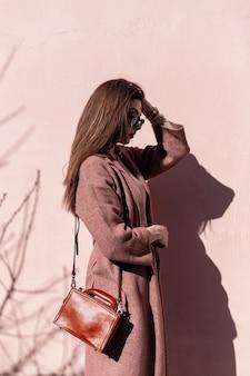 Modne bardzo luksusowe młoda kobieta model w stylowy płaszcz z torebką w okularach przeciwsłonecznych pozowanie w pobliżu ściany różowy w słoneczny dzień. urocza dziewczyna w pięknych ubraniach cieszy się promieniami słonecznymi na zewnątrz.
