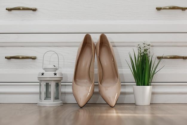 Modne beżowe buty na wysokim obcasie do wnętrz. para klasycznych butów damskich na obcasach. szczegóły ślubu z bliska