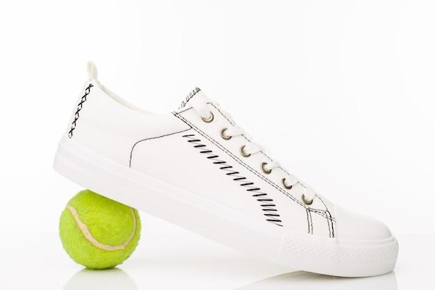 Modne białe buty do chodzenia z piłką tenisową na białym.
