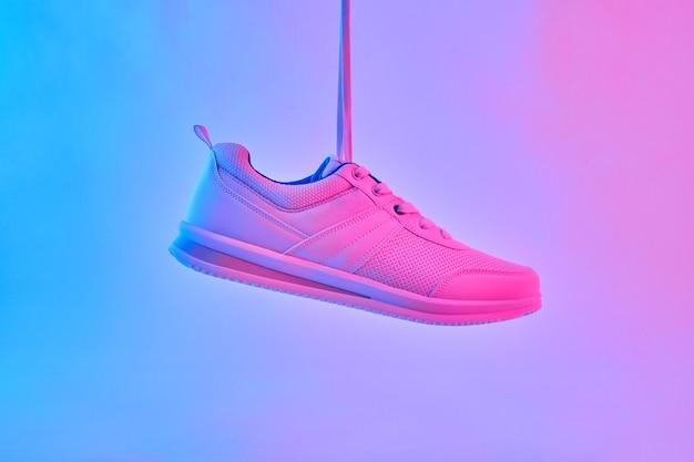 Modne białe trampki w neonowym świetle buty sportowe na trening na siłowni kreatywny minimalizm