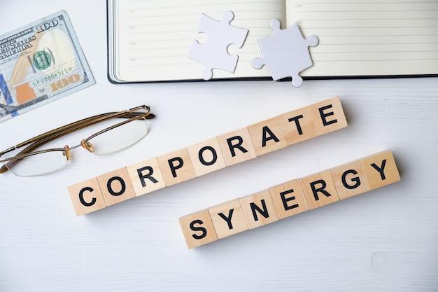 Modne biznesowe hasło - synergia korporacyjna. widok z góry na notatnik, dolar z drewnianymi klockami. widok z góry.
